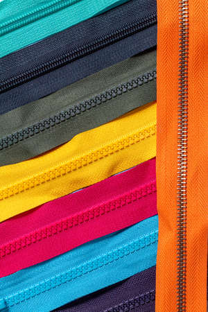 Pack lot of colorful plastic and metal zippers stripes with sliders pattern for handmade sewing tailoring on the blue denim background close up selective focus