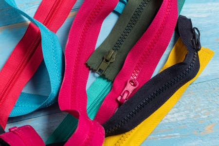 Pack lot of colorful plastic and metal zippers stripes with sliders pattern for handmade sewing tailoring on the blue painted wooden background close up selective focus