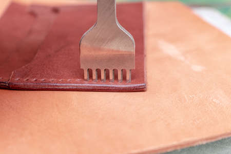 Making holes in leather with puncher tool. Sewing wallet. Stock fotó