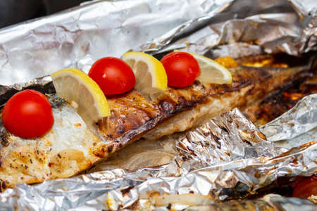 Fried mackerel on the foil with lemon and cherry tomatoes healthy delicious tasty food close up selective focus