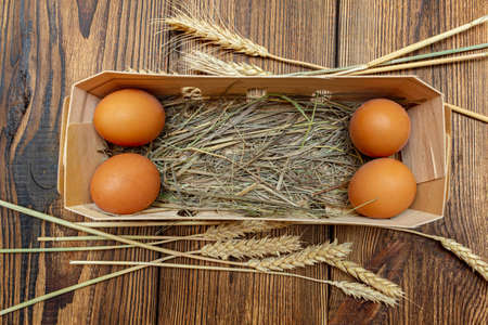 farm brown eggs with straw in birch bark box wooden background close-up