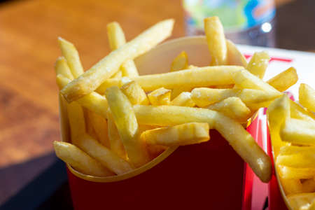 Eating fast food French fries potatoes, unhealthy fast food. Calories fat. Standard-Bild