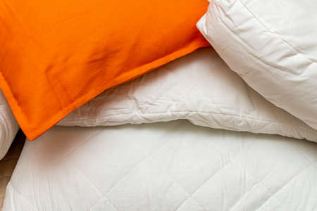 White and beige packed pile of the linen bedclothes blanket with pillow and bedding sheets 免版税图像