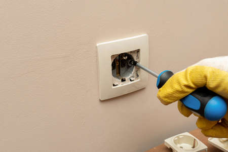 Replacing, installing an electrical socket, outlet with hands in protective rubber gloves