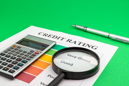 Credit rating with pen, calculator and magnifying glass on a green table.