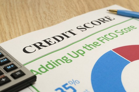 Credit score report with calculator, notebook and pen on a table.