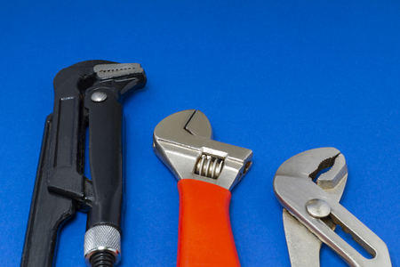 Plumbing work tools on a blue background, professional keys. Reklamní fotografie