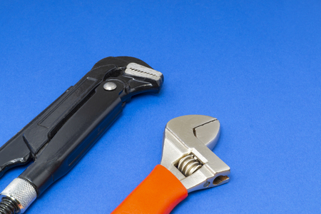 Plumbing work tools on a blue background, professional keys. Imagens