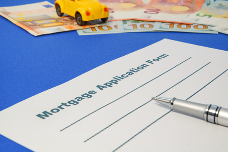 Mortgage application form with money, pen and car on the blue background. Stock fotó