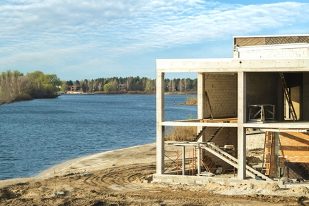 House under construction on the river bank - landscape view. Stock Photo