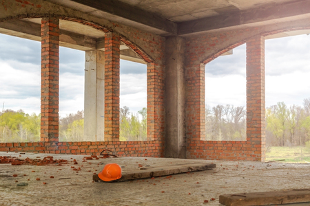 House under construction - view inside with large Windows and helmet on the floor. Stock Photo