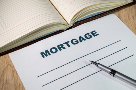 Blank sheet Mortgage and pen on bright wooden office desk.