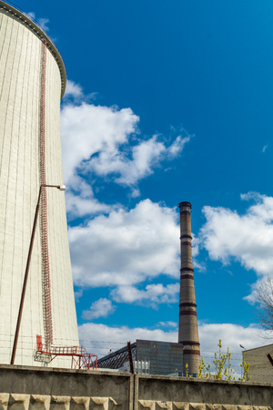 Thermal power station, industrial landscape with big chimney against the blue sky. Banco de Imagens