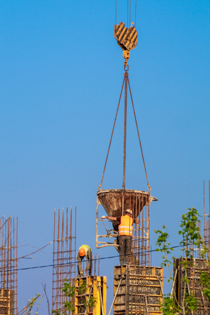 Home construction - concrete workers served by the crane on the sky background Imagens