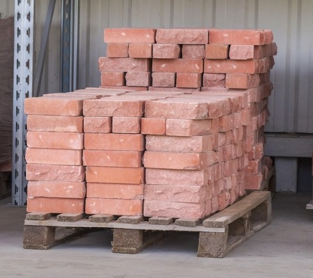 Red clay bricks are stacked on wooden pallets. Production of bricks from clay. Stock Photo