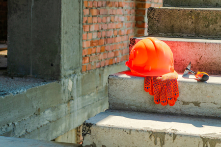 A pair of gloves and a Masons helmet at the construction site of a red brick house.