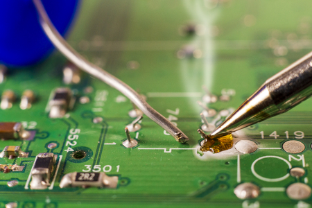Electronics manufacturing services, soldering of electronic board close-up. 版權商用圖片