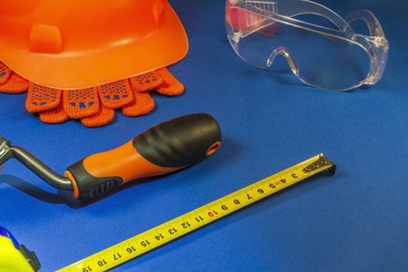 Protective helmet, gloves, tape measure and tool on a blue table with space for advertising.