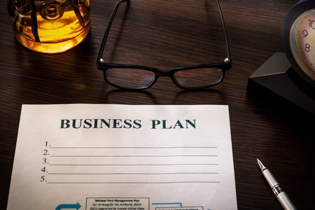 Strategy business plan with pen, clock, glasses and notepad on brown table closeup.