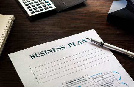 Strategy business plan with pen, clock, calculator and notepad on brown table closeup.