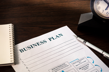 Strategy business plan with pen, clock and notepad on brown table closeup.