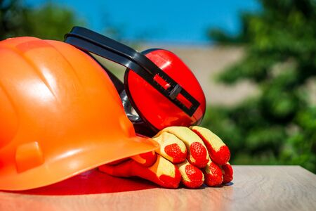 Protective helmet, headphones, gloves, glasses on a wooden table, against the background of nature. Construction site safety. Stok Fotoğraf
