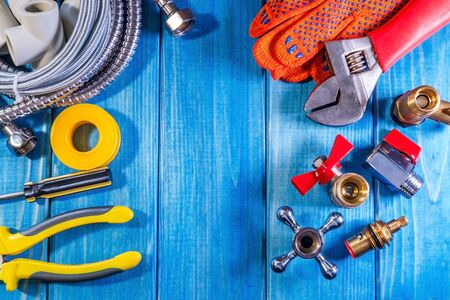 Different plumbing supplies and tools on a blue wooden background close-up. Suitable for the site of the repair of plumbing products.