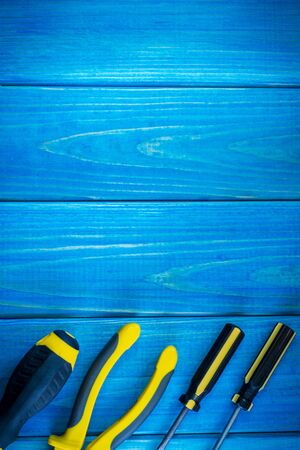 Hand tool on blue wooden background for homework. Kit for household works or for a locksmith.