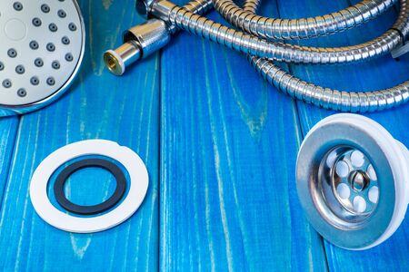 Accessories for plumbing repairs or washing in the kitchen on a wooden vintage background.