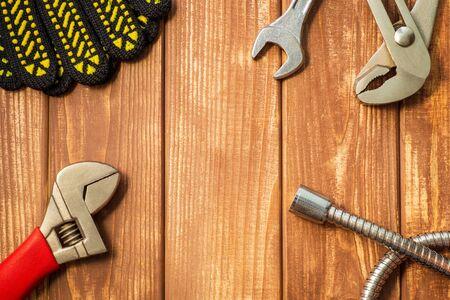 Ensemble d'outils nécessaire pour les plombiers sur un fond en bois en bois vintage. Également un espace pour la publicité.