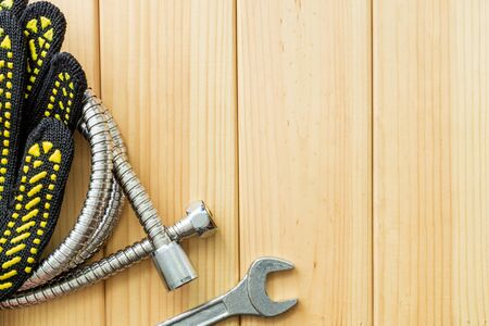 Necessary set of tools for plumbers on a wooden background. Also space for advertising.