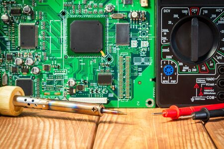 Services for the production of electronics and repair of electronic boards. Wooden background.