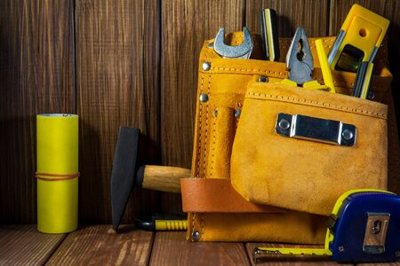 Tools and instruments in leather bag isolated on vintage wooden