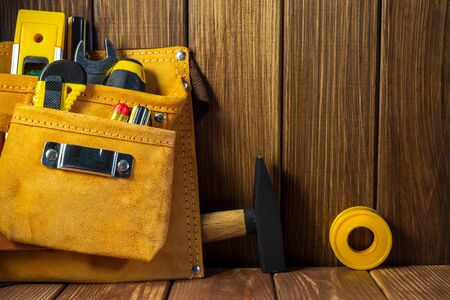 Tools and instruments in leather bag on vintage wooden