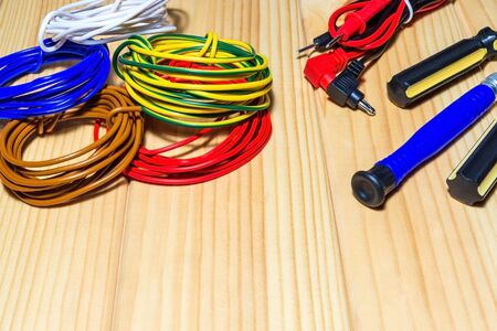 Tools and spare parts for electrician - wiring, tester, screwdrivers on wooden boards.