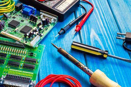 Dienstleistungen für die Herstellung von Elektronik und Reparatur auf einem hölzernen Blau