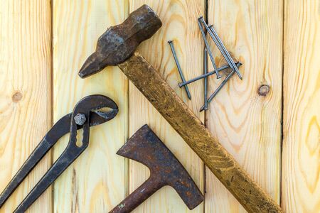 Rusty old tools are laid out on a wooden Foto de archivo - 129716306