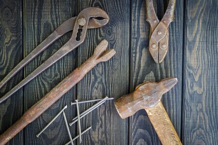 Rusty old tools are laid out on black vintage wood Foto de archivo - 129716315