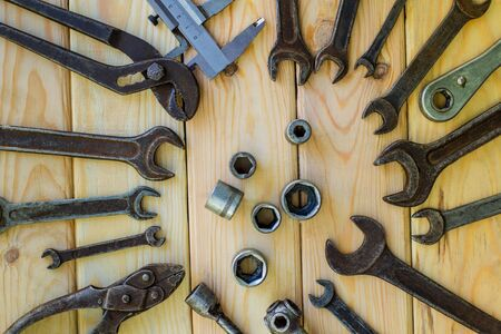 Rusty old tools are laid out on a wooden Foto de archivo - 129716006