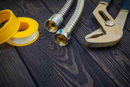Plumbing tools for connecting water hoses on a black vintage wooden