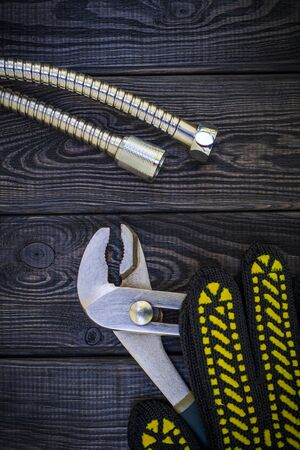Plumbing tools and gloves for connecting water hoses on a black vintage wooden Stock fotó