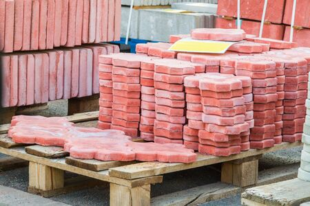 Red tiles piled in pallets, warehouse paving slabs in the factory for its production 免版税图像 - 130718304