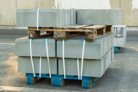 Gray tiles piled in pallets, warehouse paving slabs in the factory for its production