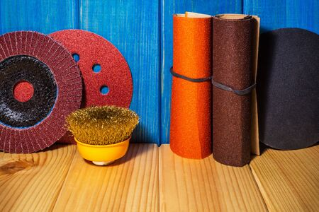 Set of abrasive tools and sandpaper blue wood background. The wizard is used for grinding items.
