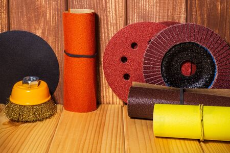 Set of abrasive tools and sandpaper on brown vintage wood background. The wizard is used for grinding items.