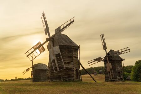 Old wooden windmills at sunset Ukrainian style that were popular in the last century Standard-Bild