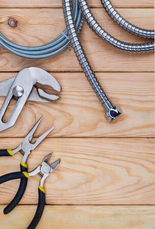 Necessary set of tools for plumbers on wooden background indispensable for master