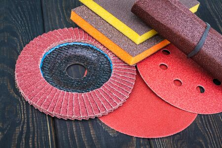 Set of abrasive tools and sandpaper on black vintage wooden