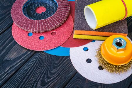 Set of abrasive tools different colors and sandpaper on black vintage wooden Stock Photo