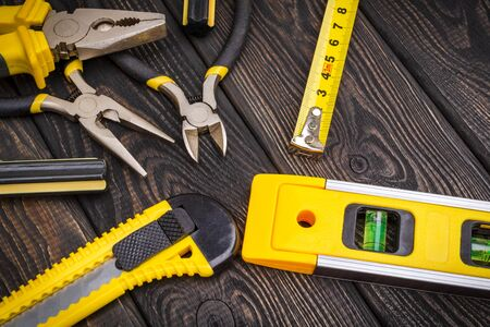 Tools for master builder and accessories on a wooden black vintage background